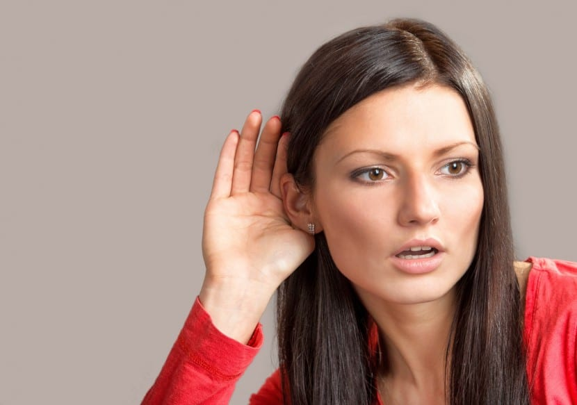 Portrait of a listening girl on gray background